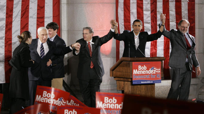 FILE - In this Thursday, Nov. 2, 2006 file photograph, Sen. Robert Menendez, D-N.J.,  third from right, raises arms with Sen. Barack Obama, D-Ill., second from right, New Jersey Gov. Jon Corzine, right, Sen. Frank Lautenberg, D-N.J., second from left, during a campaign rally for Menendez in Hoboken, N.J.  Also in the group are Menendez' son, Rob, third from left, and his daughter, Alicia, left. Menendez is running against state Sen. Tom Kean Jr, for U.S. Senate from New Jersey. In January 2013, the Sen. Menendez's role in Washington grew as he became chairman of the Foreign Relations Committee and was a major player in a bipartisan Senate plan to overhaul the nation's immigration laws. At the same time, he has been in the familiar situation of fending off charges of impropriety. He's repaid a donor for travel in a private jet and tried to shoot down stories that he's patronized prostitutes in the Dominican Republic. (AP Photo/Mike Derer, File)