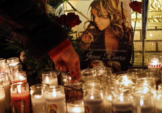 A woman adjusts a flower in front of candles and pictures displayed in tribute to singer Jenni Rivera at the Plaza Mexico shopping center in Lynwood, Calif., early Monday, Dec. 10, 2012. Authorities h