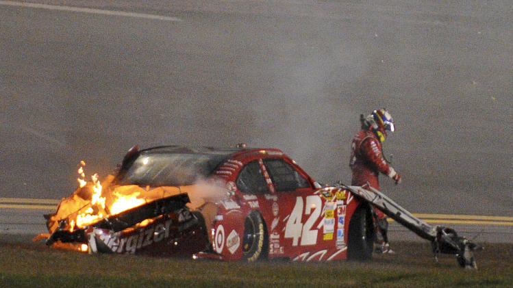 Juan Pablo Montoya, of Colombia, walks from his car after it collided with a track-drying truck during the NASCAR Daytona 500 auto race at Daytona International Speedway in Daytona Beach, Fla., Monday, Feb. 27, 2012. (AP Photo/Rob Sweeten)