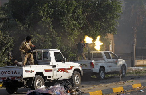 Rebel fighters shoot during street fighting in the Abu Salim district in Tripoli, LIbya, Thursday, Aug. 25, 2011.  Fighting continued to rage Thursday between rebels and forces loyal to Moammar Gadhafi.(AP Photo/Sergey Ponomarev)