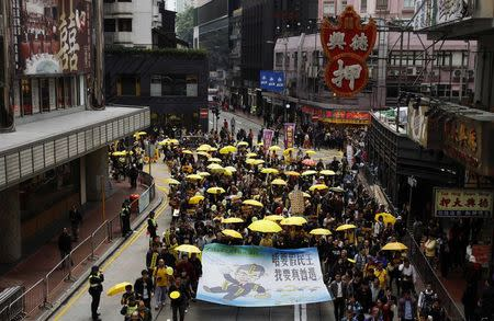 Protesters carry yellow umbrellas, the symbol of the Occupy movement, and a banner as they march on a street in Hong Kong