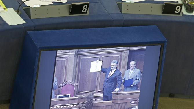 Ukraine's President Poroshenko is seen on a tv monitor as displays a signed landmark association agreement with the European Union during a live video conference between Kiev and Strasbourg, at the European Parliament in Strasbourg