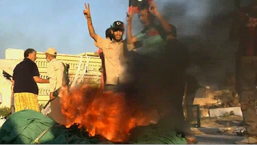 In this image from video rebel fighters wave a rebel flag over a burning green Gadhafi regime flag they had just torn down as they celebrate victory on a street in Zawiya, Libya Friday Aug.19 2011 after they battled for control of the strategic central square against forces loyal to  Moammar Gadhafi. Rebel forces  were reported to have expelled government forces from  Zawiya, a coastal city just 30 miles (50 kilometers) west of Tripoli, on Saturday Aug. 20. They also claim to have captured two more towns - Zlitan in the west and Brega in the east. The momentum in the six-month-old Libyan civil war now appears to have firmly swung in the rebels favor after months of near deadlock. (AP Photo/Sky via APTN)