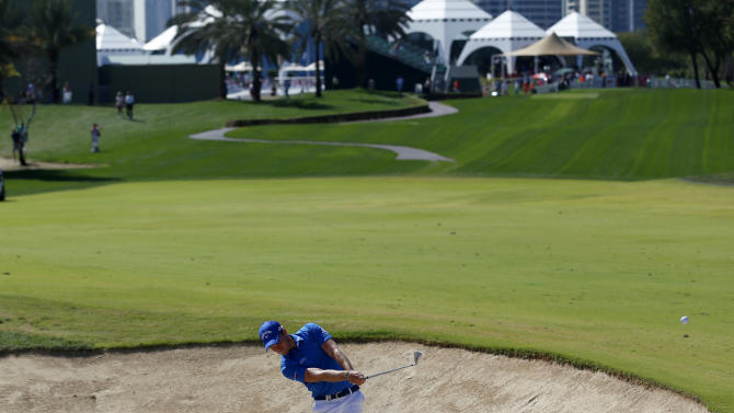 Danny Willett of England hits the ball out of the bunker on the first hole during the Dubai Desert Classic golf championship