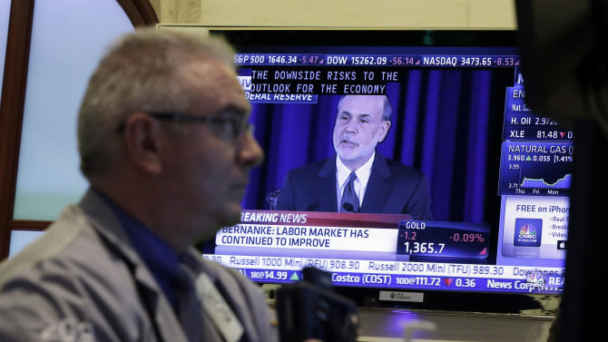 Fed Chairman Ben Bernanke is on a television screen as trader James Dresch works in a booth on the floor of the New York Stock Exchange Wednesday, June 19, 2013.  The Federal Reserve offered a hint Wednesday that it's moving closer to slowing its bond-buying program, which is intended to keep long-term interest rates at record lows. (AP Photo/Richard Drew)