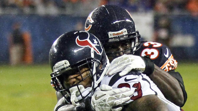 Houston Texans running back Arian Foster is tackled by Chicago Bears cornerback Charles Tillman (33) during the first half an NFL football game, Sunday, Nov. 11, 2012, in Chicago. (AP Photo/Charles Rex Arbogast)