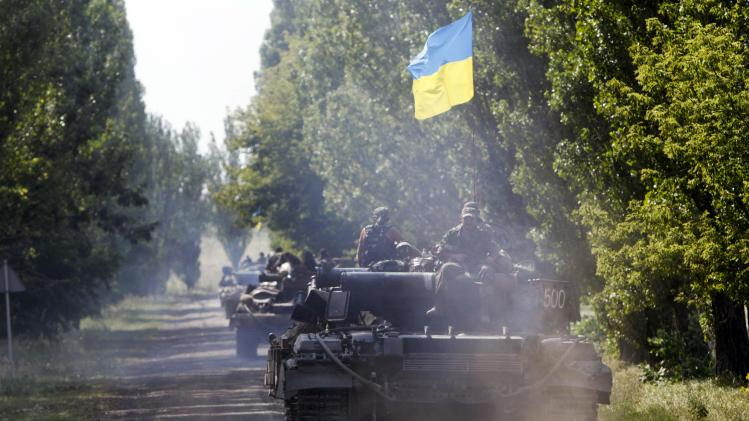 Ukrainian tanks move along a road near Eastern Ukrainian village of Novoselivka Persha