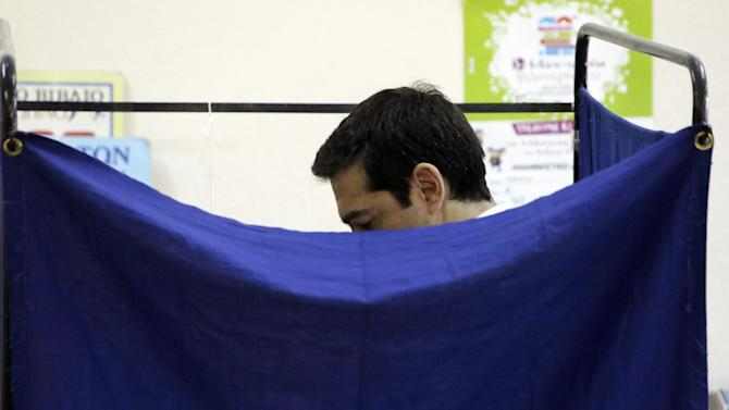 Greece's Prime Minister Alexis Tsipras casts his vote at a polling station in Athens, Sunday, July 5, 2015. Greeks began voting early Sunday in a closely-watched, closely-contested referendum, which the government pits as a choice over whether to defy the country's creditors and push for better repayment terms or essentially accept their terms, but which the opposition and many of the creditors paint as a choice between staying in the euro or leaving it. (AP Photo/Petros Giannakouris)