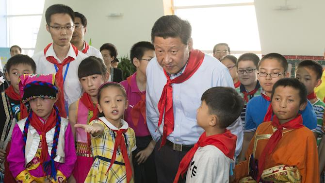In this May 29, 2013 photo released by China's Xinhua News Agency, Chinese President Xi Jinping, center, takes part in a children's activity in Beijing, China. In nearly 10 months as China's leader, Xi Jinping has projected himself as a man of the people in a Mao Zedong-inspired propaganda push to connect with an alienated public. (AP Photo/Xinhua, Li Xueren) NO SALES