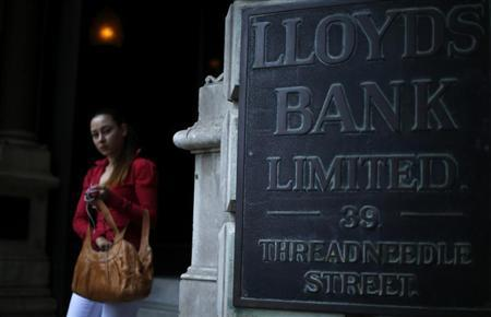 A woman leaves a branch of Lloyds Bank in the City of London