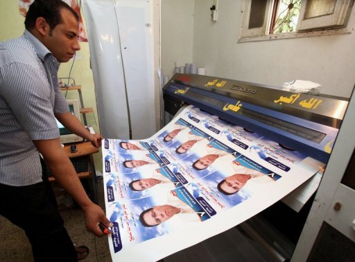 A Libyan worker rolls freshly-printed election campaign posters for an independent candidate in Tripoli