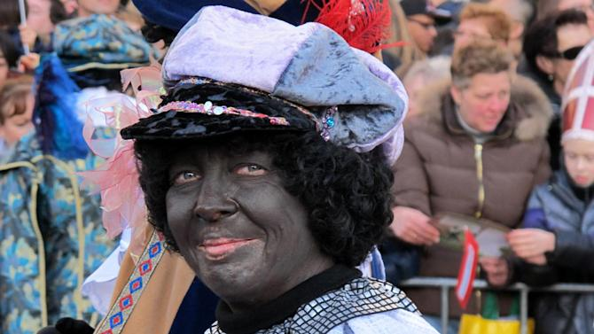 "In this photo taken Sunday, Nov. 18, 2012 a person dressed as ""Zwarte Piet"" or ""Black Pete"" attend a parade after St. Nicholas, or Sinterklaas, arrived by boat in Amsterdam, Netherlands. Foreigners visiting the Netherlands in winter are often surprised to see that the Dutch version of St. Nicholas' little helpers resemble a racist caricature of a black person. The overwhelming majority of Dutch, who pride themselves on tolerance, are fiercely devoted to their holiday tradition and say ""Zwarte Piet"", whose name means ""Black Pete"", is absolutely harmless, a fictional figure who does not represent any race. But now a growing group of Dutch natives are questioning whether this particular part of the tradition should be changed. (AP Photo/ Margriet Faber)"
