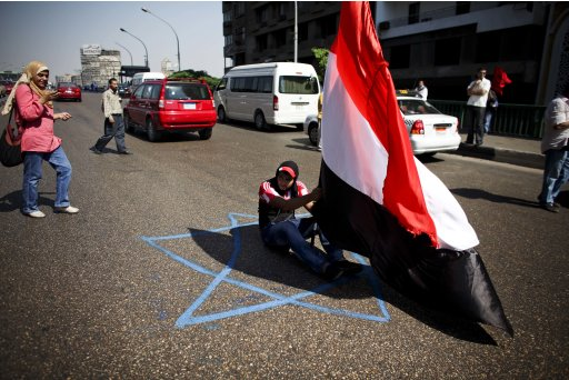 An Egyptian man sits with his national flag on top of a Star of David, which is also part of the Israeli flag, during a protest in front of the Israeli embassy in Cairo, Egypt, Friday, Aug. 19, 2011. On Thursday, gunmen who appear to have originated in Gaza and crossed into southern Israel through the Egyptian desert ambushed civilian vehicles traveling on a remote road, killing eight people. Six were civilians, and two were members of Israeli security forces responding to the incursion. Additionally, Egyptian officials said five Egyptian security personnel died as a result of Thursday's gunbattles. (AP Photo/Tara Todras-Whitehill)