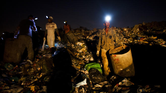In this May 29, 2012 photo, Walter Barbosa, 60, waits for a trash truck to unload at Jardim Gramacho, one of the world's largest open-air landfills, in Rio de Janeiro, Brazil. Jardim Gramacho, a vast, seaside mountain of trash where thousands of people made a living sorting through the debris by hand, is closing after three decades in service. (AP Photo/Victor R. Caivano)