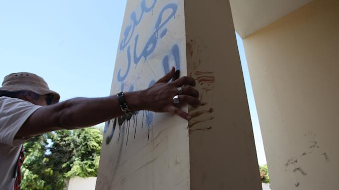 """A Libyan man explains that the bloodstains on the column are from one the American staff members who grabbed the edge of the column while he was evacuated, after an attack that killed four Americans, including Ambassador Chris Stevens on the night of Tuesday, Sept. 11, 2012, in Benghazi, Libya, Thursday, Sept. 13, 2012.  The American ambassador to Libya and three other Americans were killed when a mob of protesters and gunmen overwhelmed the U.S. Consulate in Benghazi, setting fire to it in outrage over a film that ridicules Islam's Prophet Muhammad. Ambassador Chris Stevens, 52, died as he and a group of embassy employees went to the consulate to try to evacuate staff as a crowd of hundreds attacked the consulate Tuesday evening, many of them firing machine-guns and rocket-propelled grenades. Arabic writing reads, """" Villa of Jamal al Beshary"""". which was written by the owner to protect the property from another attack. (AP Photo/Mohammad Hannon)"""