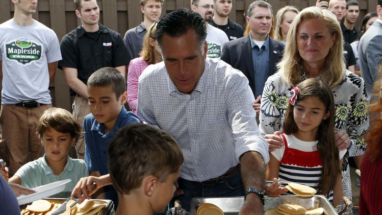 Mitt Romney serve pancakes while attending a pancake breakfast at Mapleside Farms in Brunswick