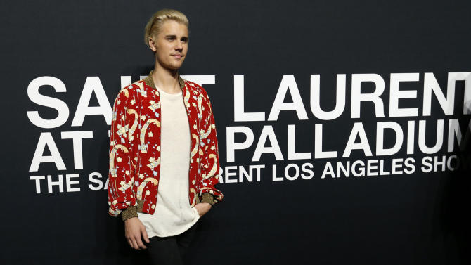 Recording artist Bieber poses as he arrives for the Saint Laurent fall collection fashion show at the Hollywood Palladium in Los Angeles