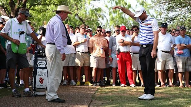 Keegan Bradley takes a drop as a rules official looks on during the second round of the 2013 HP Byron Nelson Championship at the TPC Four Seasons Resort (AFP)