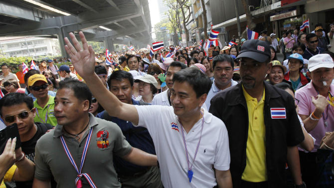 """Democrat leader and former Prime Minister Abhisit Vejjajiva waves as he marches with anti-government protesters in Bangkok, Thailand Monday, Dec. 9, 2013. Thai Prime Minister Yingluck Shinawatra announced Monday she will dissolve the lower house of Parliament and call elections in an attempt to calm the country's deepening political crisis. The surprise move came as 100,000 protesters vowing to overthrow her government marched through the streets of Bangkok for a """"final showdown."""" (AP Photo/Greg Baker)"""
