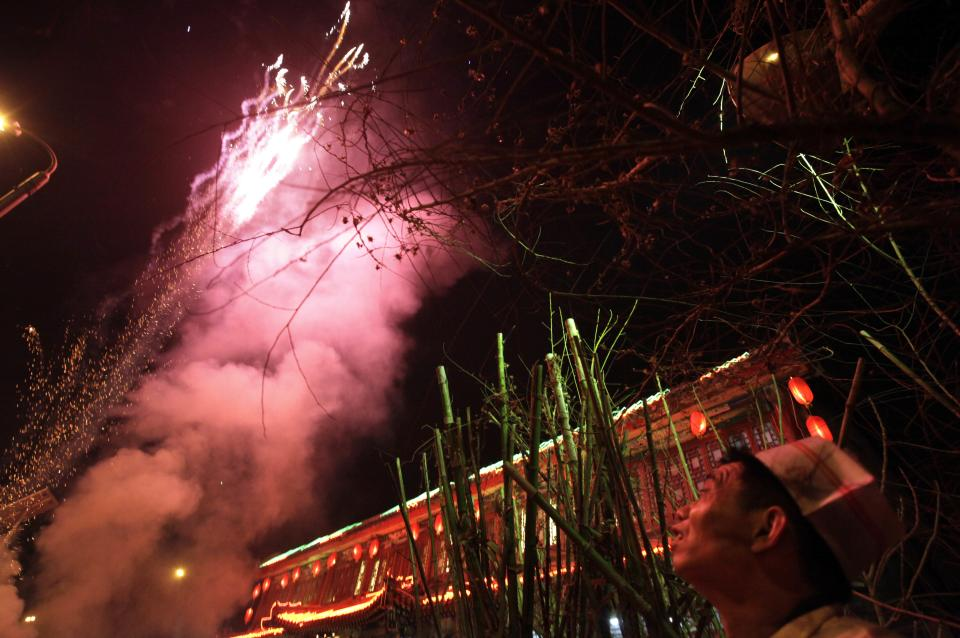 A chef with a restaurant enjoys fireworks to celebrate the fifth day of Chinese New Year in Beijing, China, Monday, Feb. 7, 2011. (AP Photo/Ng Han Guan)