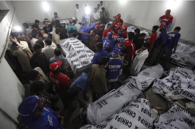 Rescue workers and residents gather at the morgue to identify relatives at a morgue after a bomb blast in a residential area in Karachi