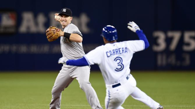 New York Yankees' Stephen Drew throws to first after Toronto Blue Jays' Ezequiel Carrera (3) is forced out at second on a fielder's choice by Blue Jays' Devon Travis during the third inning of a baseball game Tuesday, May 5, 2015, in Toronto. (AP Photo/The Canadian Press, Frank Gunn)