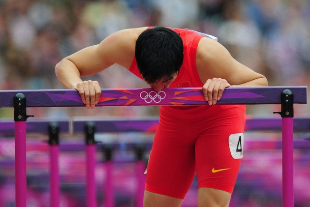 Liu Xiang kisses the final hurdle after failing to finish the 110-meter hurdles in London.