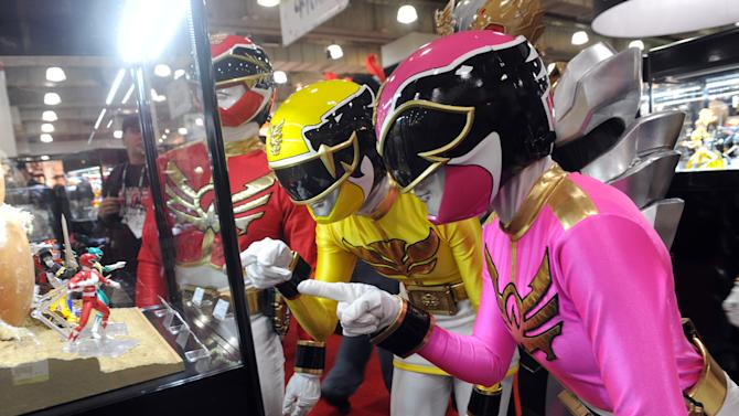The Power Rangers check out their 20th anniversary collectibles at the American International Toy Fair, Sunday, Feb. 10, 2013, in New York. Saban Brands is celebrating the 20th anniversary of the Power Rangers franchise at the show. (Diane Bondareff/Invision for Saban Brands/AP Images)