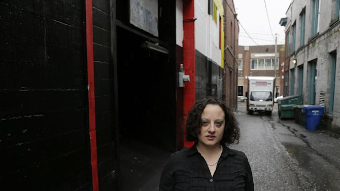 """In this Friday, April 19, 2013 photo, Sarah Toce, editor of a daily online news magazine """"The Seattle Lesbian,"""" poses for a photo in Seattle's Capitol Hill neighborhood, in an alleyway that has been the site of fights and other violence against gay men. Even as society has become more accepting of homosexuality overall, longstanding research has shown more societal tolerance for lesbians than gay men, and that gay men are significantly more likely to be targets of violence. (AP Photo/Ted S. Warren)"""