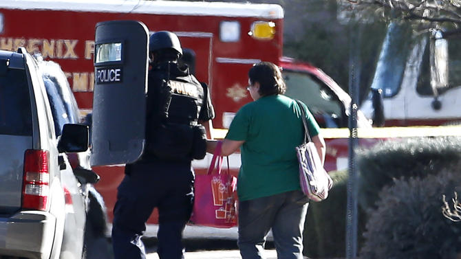 A member of the Phoenix Police Department SWAT team leads a female neighbor away to safety, as the the SWAT team prepares to enter the home of a suspected gunman who opened fire at a Phoenix office building, wounding three people, one of them critically, and setting off a manhunt that led police to surround his house for several hours before they discovered he wasn't there, Wednesday, Jan. 30, 2013, in Phoenix.  Authorities believe there was only one shooter, but have not identified him or a possible motive for the shooting. They don't believe the midmorning shooting at the complex was a random act. (AP Photo/Ross D. Franklin)