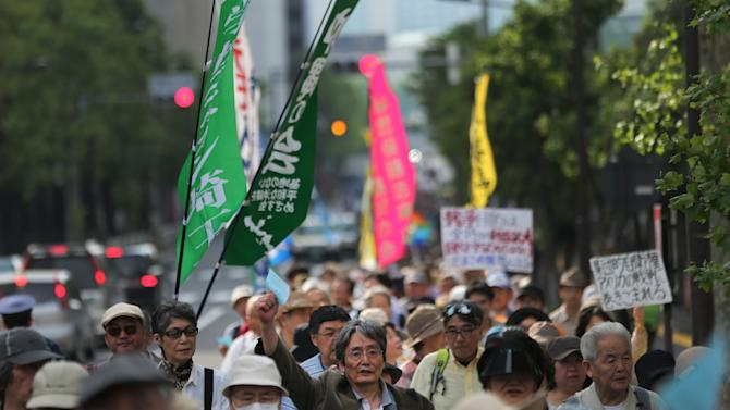 Hundreds of people march vowing to protect the constitution in Tokyo, Saturday, May 3, 2014. Japan marked the 67th anniversary of its postwar constitution Saturday with growing debate over whether to revise the war-renouncing charter in line with Prime Minister Shinzo Abe's push for an expanded role for the military. (AP Photo/Eugene Hoshiko)
