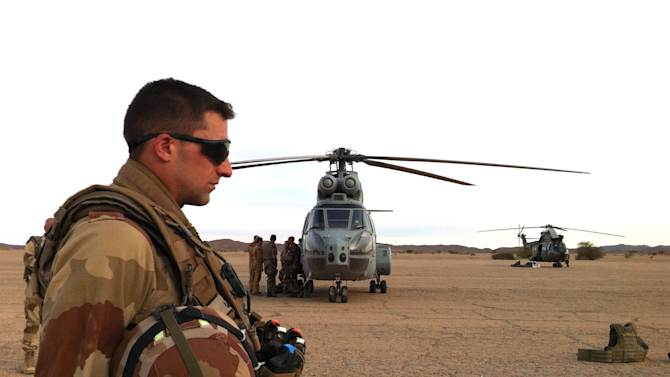 In this photo made Friday Feb. 6, 2013, French soldiers walk on the tarmac of the airport in the remote desert city of Tesalit, northern Mali. President of the government body representing the area of Tessalit, Aicha Belco Maiga, confirmed by telephone from her home in Bamako that her town had been retaken by French forces. (AP Photo)