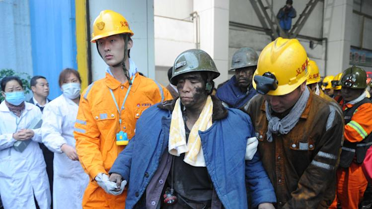 In this photo released by China's Xinhua news agency, rescued miners are helped to walk out of a coal mine after being trapped underground for more than 30 hours at the Qianqiu Coal Mine in Sanmenxia City, Henan province, on Saturday Nov. 5, 2011. Rescuers have pulled 42 more miners to the surface and are searching for several more who were trapped after a cave-in at the coal mine in central China. (AP Photo/Xinhua, Zhu Xiang) NO SALES