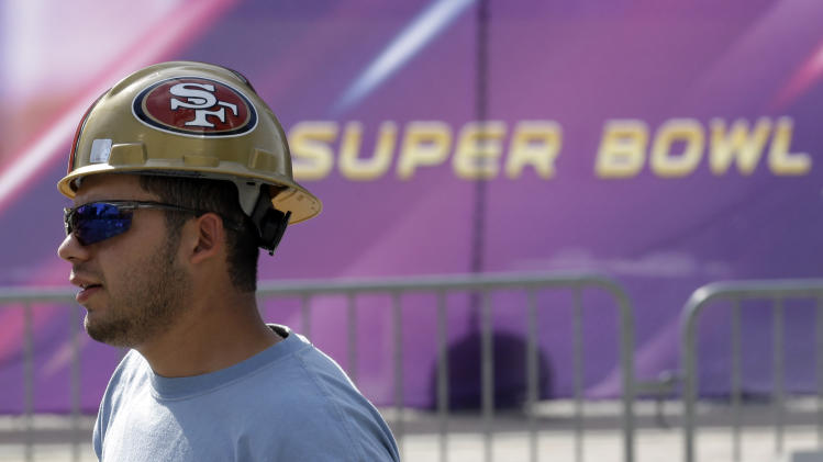A worker in a San Francisco 49ers hard hat walks outside of the Mercedes-Benz Superdome as preparations take place for the NFL Super Bowl XLVII football game on Sunday, Jan. 27, 2013, in New Orleans. The Baltimore Ravens and San Francisco 49ers are scheduled to play in Super Bowl XLVII on Sunday, Feb. 3. (AP Photo/Patrick Semansky)