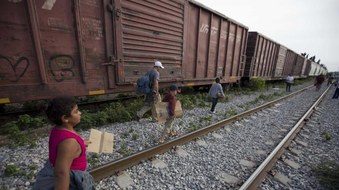 FILE - In this July 12, 2014 file photo, migrants walk along the rail tracks after getting off a train during their journey toward the U.S.-Mexico border in Ixtepec, Mexico. Many of the immigrants recently flooding the nation's southern border say they're fleeing violent gangs in Central America. These gangs were a byproduct of U.S. immigration and Cold War policies, specifically growing from the increase in deportations in the 1990s. With weak dysfunctional governments at home, U.S. street gang culture easily took hold and flourished in these countries. (AP Photo/Eduardo Verdugo)