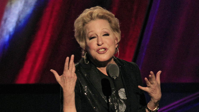 FILE - In this April 14, 2012 file photo, Bette Midler introduces the late Laura Nyro for induction into the Rock and Roll Hall of Fame in Cleveland. An online campaign to raise money so Native American tribes in South Dakota can purchase land they consider sacred has gained steam with a growing list of celebrities backing the effort. P Diddy and Midler have tweeted their support for the effort to purchase nearly 2,000 acres in the Black Hills of South Dakota. They join actor Ezra Miller and hip-hop producer Sol Guy, who appeared in a recent video online with drawing attention to the effort. (AP Photo/Tony Dejak, File)