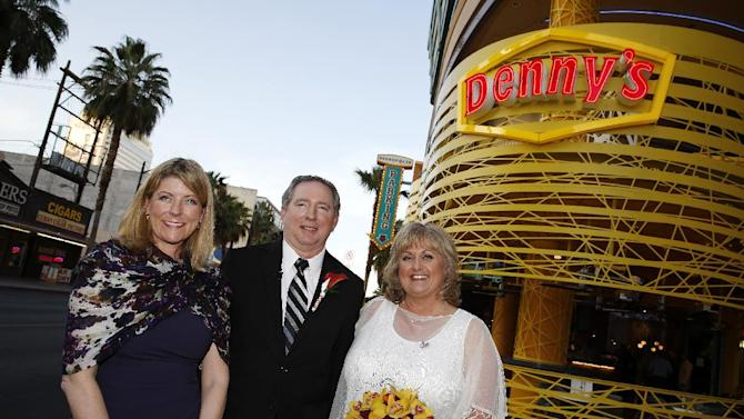 IMAGE DISTRIBUTED FOR DENNY'S - From left, Denny's Chief Marketing Officer, Frances Allen, and newlywed couple Steven Keller and Nancy Keller pose for photos following Denny's on Fremont's first wedding ceremony on Wednesday, April 3, 2013 in Las Vegas. Denny's selected the Keller's, long-time food enthusiasts, to be the first couple to walk down the aisle in the unique wedding location. (Isaac Brekken/AP Images for Denny's)