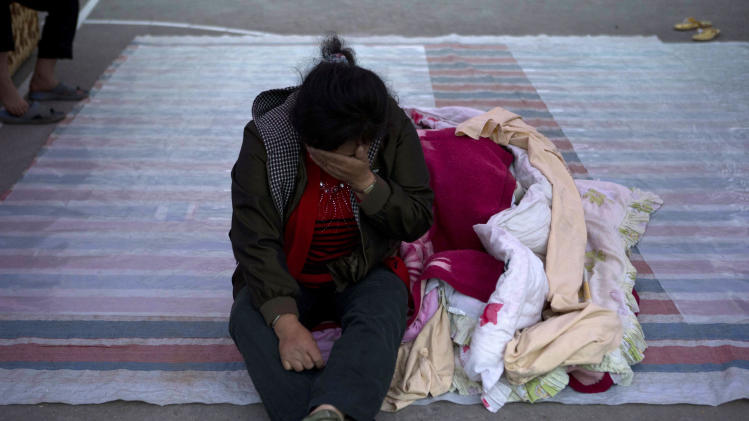 Ren Shuyong, 48, cries as she sits outside near Shangli town in southwestern China's Sichuan province, Sunday, April 21, 2013. Residents awoke Sunday after spending the night outdoors or in their cars in a town near the epicenter of a powerful earthquake that struck the steep hills of China's southwestern Sichuan province, leaving at least 160 people dead and more than 6,700 injured. (AP Photo/Ng Han Guan)