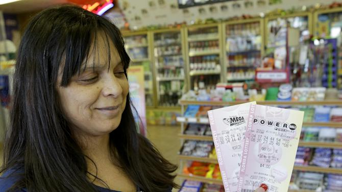 Lilly Sanchez holds up lotto tickets she purchased including a Powerball ticket seeking a payout of around $475 million,  Thursday, May 16, 2013, in Orlando, Fla.  The prize is the third largest in lottery history, and the winning numbers will be drawn on Saturday.(AP Photo/John Raoux)
