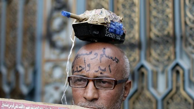 """An Egyptian protester with Arabic writing on his forehead that reads, """"Muslims and Christians, one hand,"""" attends a demonstration outside the presidential palace, in Cairo, Egypt, Wednesday, Dec. 5, 2012. Supporters of President Mohammed Morsi and opponents clashed outside the presidential palace. Wednesdayís clashes began when thousands of Islamist supporters of Morsi descended on the area around the palace where some 300 of his opponents were staging a sit-in. (AP Photo/Hassan Ammar)"""
