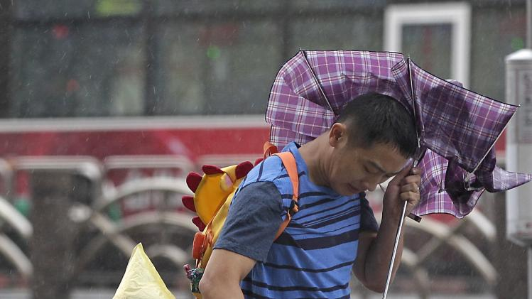 A man and a child walk against strong winds as Typhoon Matmo hits Taiwan, in Taipei