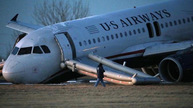 A person walks around a damaged US Airways jet at the end of a runway at the Philadelphia International Airport, Thursday, March 13, 2014, in Philadelphia. Airline officials said the flight was heading to Fort Lauderdale, Fla., when the pilot was forced to abort takeoff around 6:30 p.m., after the front landing gear failed. An airport spokeswoman said no injuries have been reported. (AP Photo/Matt Slocum)
