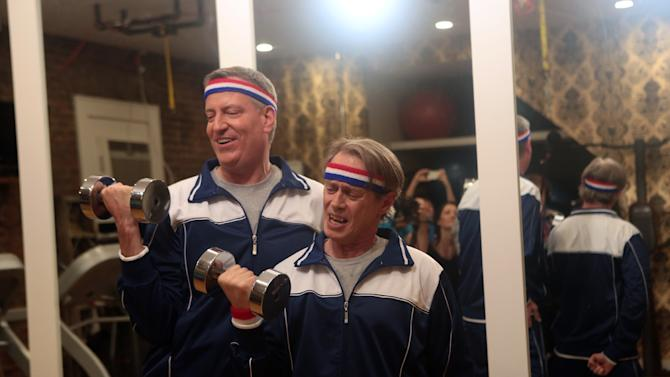 In this March 10, 2014 photo provided by the New York City Mayor's Office, Mayor Bill de Blasio, left, and actor Steve Buscemi lift weights during the production of a video to promote the city's annual Inner Circle dinner, in the Brooklyn borough of New York. The video portrays de Blasio training with Steve Buscemi to get in shape for the black-tie fundraiser in Manhattan this Saturday, March 22. It features a show by political reporters that pokes fun at the year in politics, followed by the mayor's performance, which often features a Broadway cast. This will be de Blasio's debut performance at the roast. (AP Photo/New York City Mayor's Office, Ed Reed)