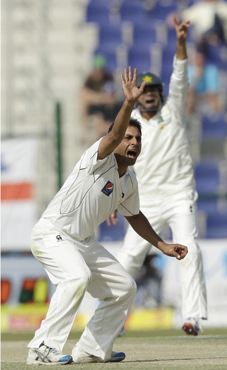 Pakistan's Abdur Rehman, left, celebrates taking the wicket of England's Kevin Pietersen, not pictured, lbw as his teammate Azhar Ali runs during the fourth day of the second cricket test match of a t