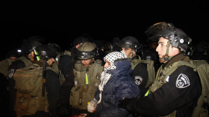 """Israeli border police evict a Palestinian activist from an area known as E-1 near Jerusalem, Sunday, Jan 13, 2013. Palestinian activists erected tents in the area on Friday saying they wanted to """"establish facts on the ground"""" to stop Israeli construction in the West Bank. The Palestinian activists were borrowing a phrase and a tactic, usually associated with Jewish settlers, who believe establishing communities means the territory will remain theirs once structures are built. (AP Photo/Nasser Shiyoukhi)"""