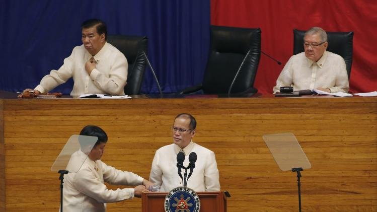 An aide pours water into a glass as Philippine President Aquino delivers his fifth SONA during the joint session of the 16th Congress at the House of Representatives of the Philippines in Quezon city, metro Manila