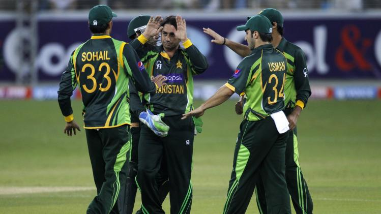 Pakistan's Saeed Ajmal celebrates with his team mates the wicket of Sri Lanka's Seekkuge Prasanna during their second Twenty20 international cricket match in Dubai