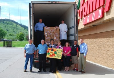 John Morrell and Family Thrift Center load 500 pounds of ham for Youth & Family Services