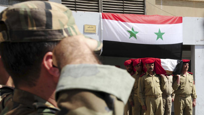 In this photo released by the Syrian official news agency SANA, a Syrian soldier salutes, left, as others carry the coffin of a comrade who was killed in recent violence in the country, during his funeral procession at a hospital in Damascus, Syria, Wednesday July 6, 2011. Syrian security forces may have committed crimes against humanity during a deadly siege of a western town in May, Amnesty International said Wednesday, citing witness accounts of deaths in custody, torture and arbitrary detention. (AP Photo/SANA) EDITORIAL USE ONLY