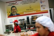 Women work at a bakery as a banner of the late Venezuelan President Hugo Chavez is seen in Ciudad Caribia outside Caracas September 26, 2013. REUTERS/Jorge Silva